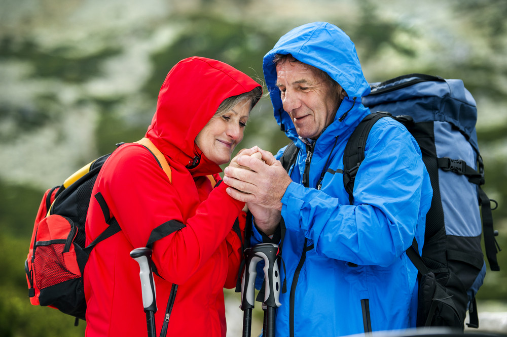 Senior tourist couple hiking at the beautiful mountains in cold weather
