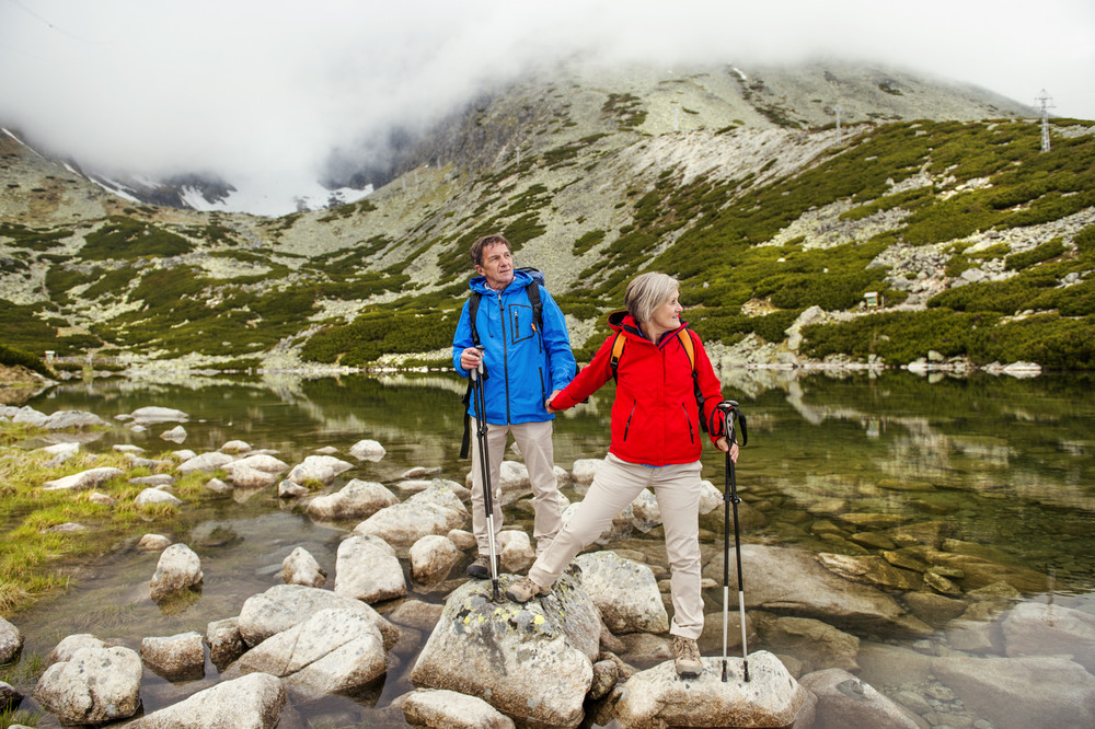 Senior tourist couple hiking at the beautiful mountains, tarn in the background