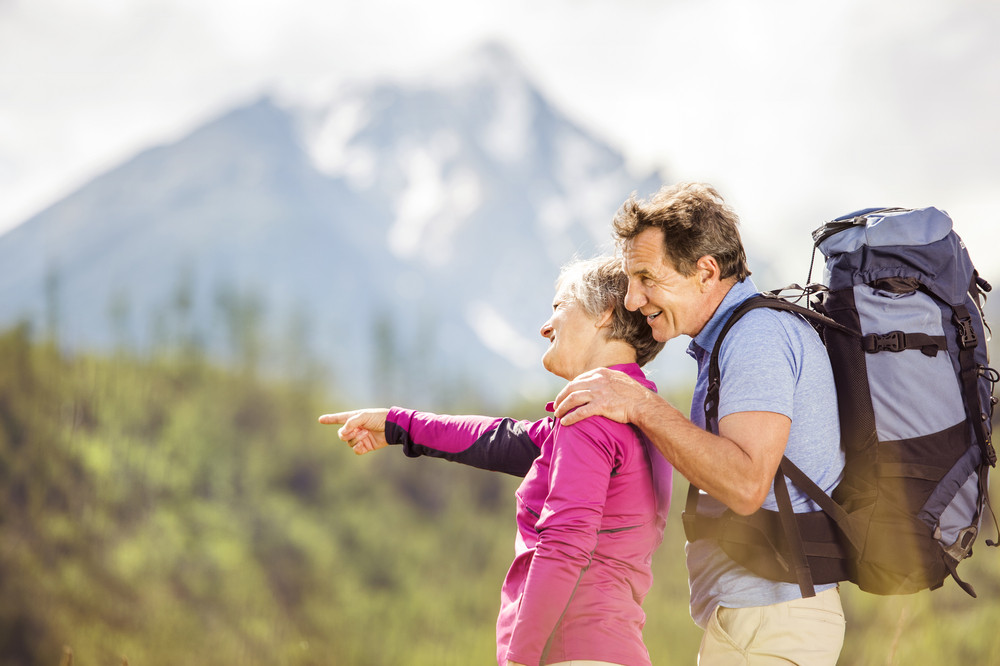 Senior tourist couple hiking at the beautiful mountains