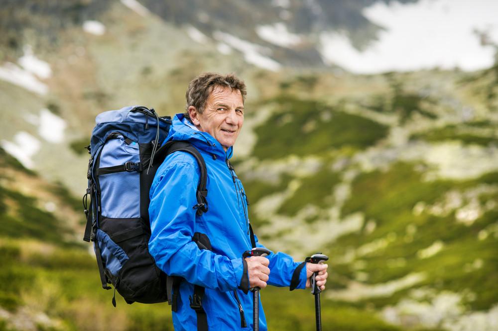 Senior tourist man hiking at the beautiful mountains