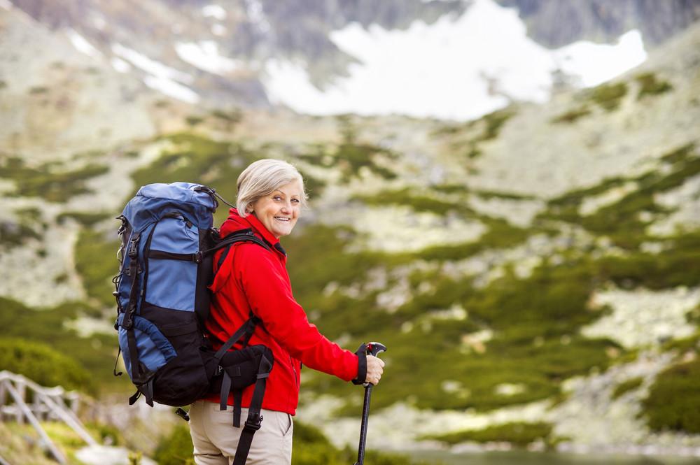 Senior tourist woman hiking at the beautiful mountains