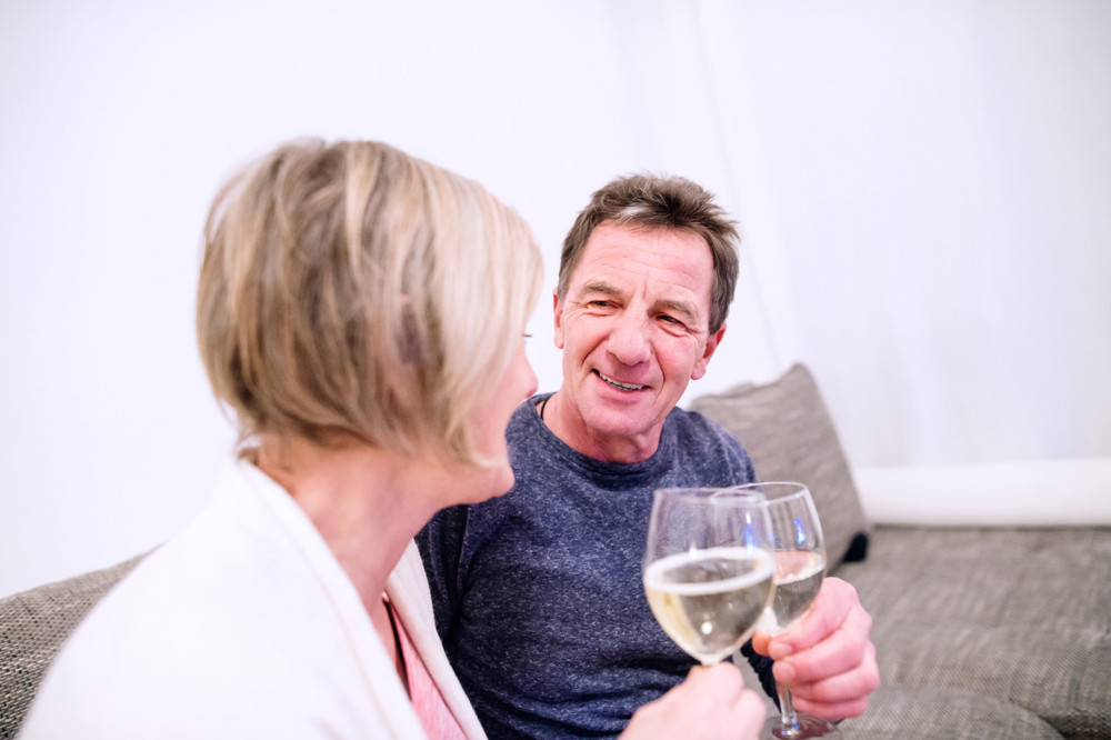 Senior woman and man sitting in living room on sofa, drinking champagne