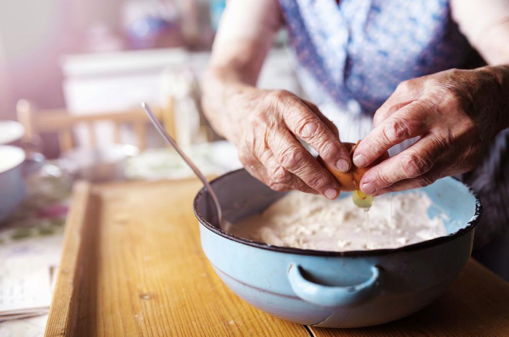 Senior woman baking pies in her home kitchen.  Adding egg.