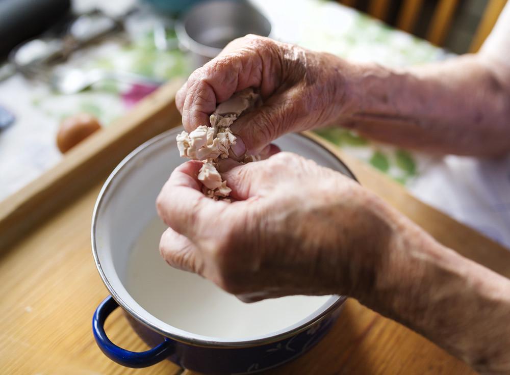 Senior woman baking pies in her home kitchen.  Adding yeast into milk.