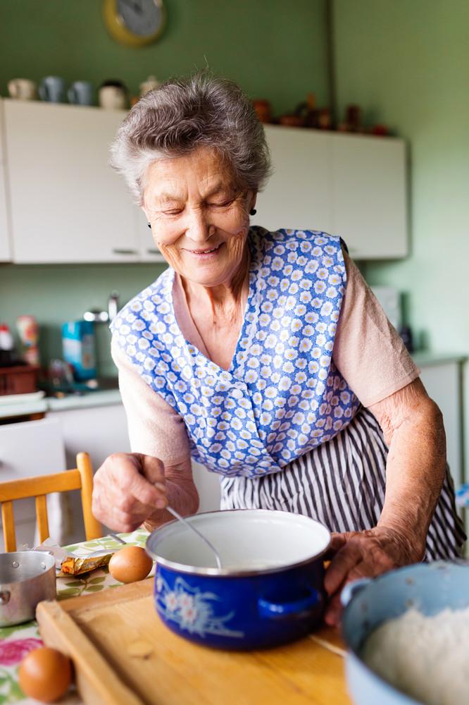 Senior woman baking pies in her home kitchen.  Measuring ingredients.