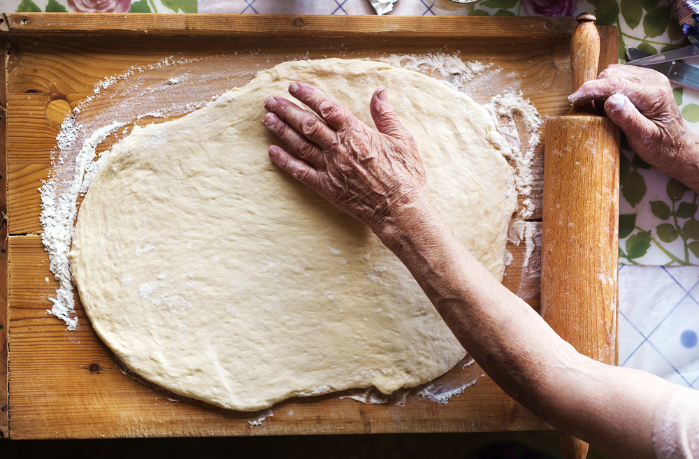 Senior woman baking pies in her home kitchen. Rolling dough using rolling pin.