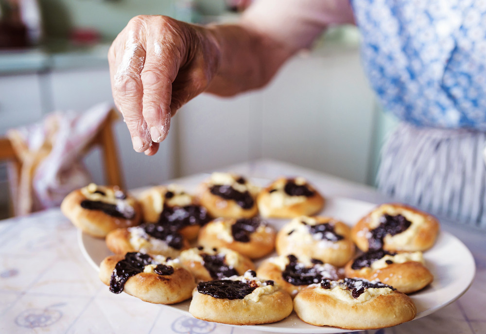Senior woman baking pies in her home kitchen. Sprinkling freshly baked buns with powdered sugar.