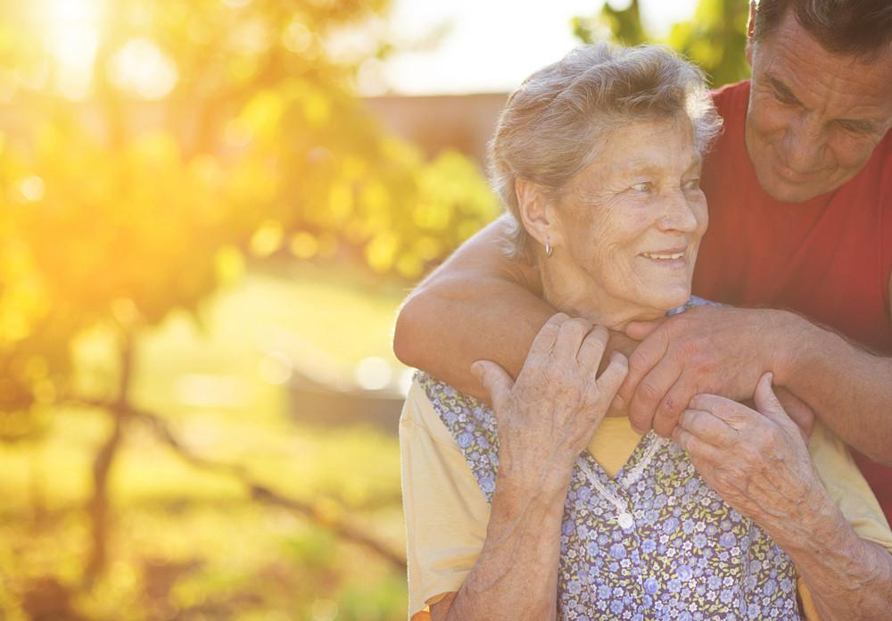 Senior woman in apron with her elderly son in her garden.