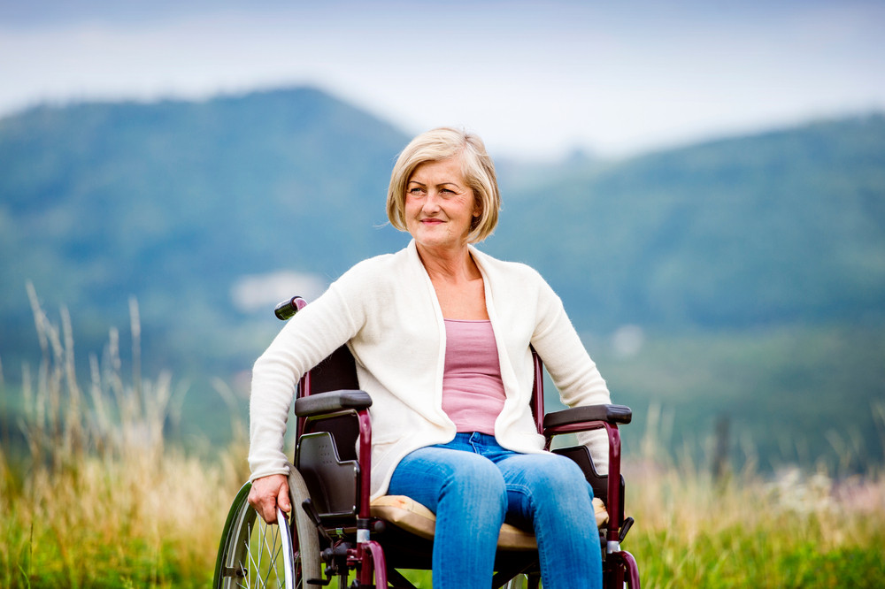 Senior woman in wheelchair outside in nature
