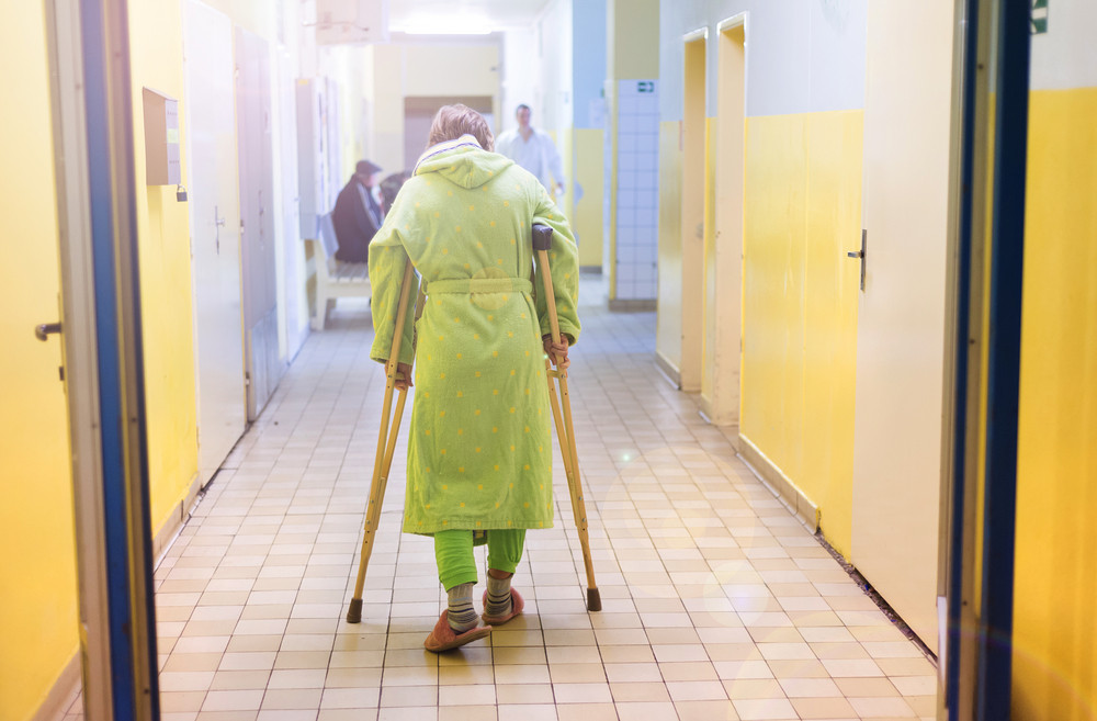 Senior woman injured sitting in the hallway of hospital holding crutches