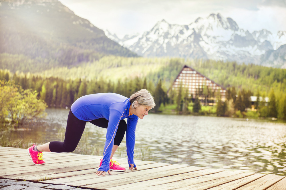 Senior woman is getting ready jogging round the tarn in beautiful mountains, hills and hotel in background