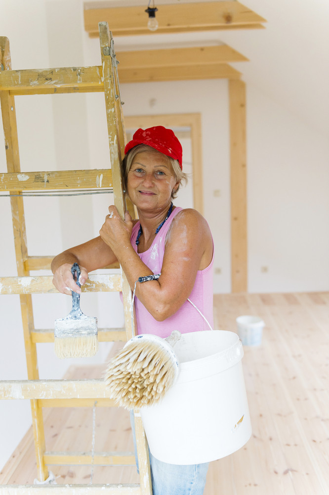 Senior woman painting wall in new house. She is using ladder.