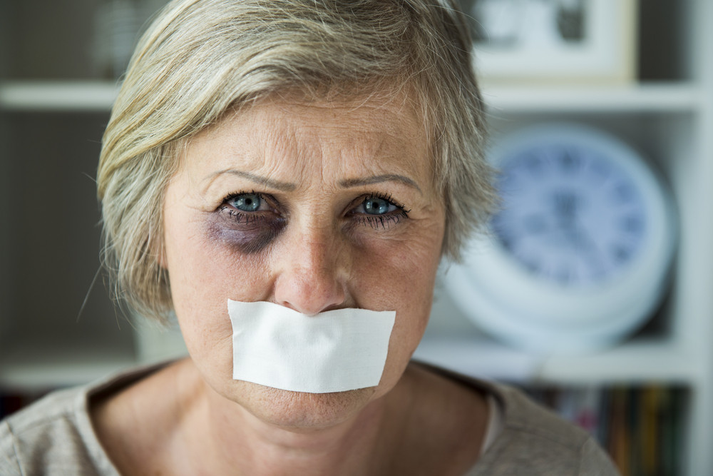 Senior woman with black eye and tape on her mouth, victim of domestic violence