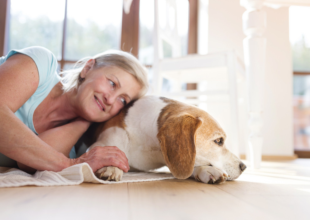 Senior woman with dog inside of her house.