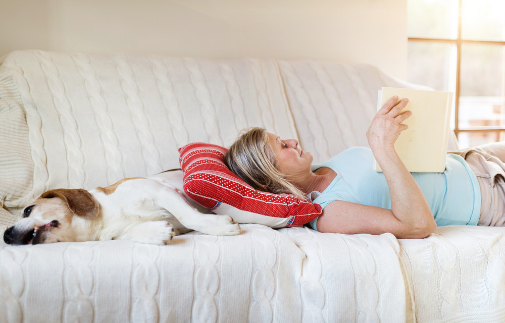 Senior woman with her dog on a couch inside of her house.