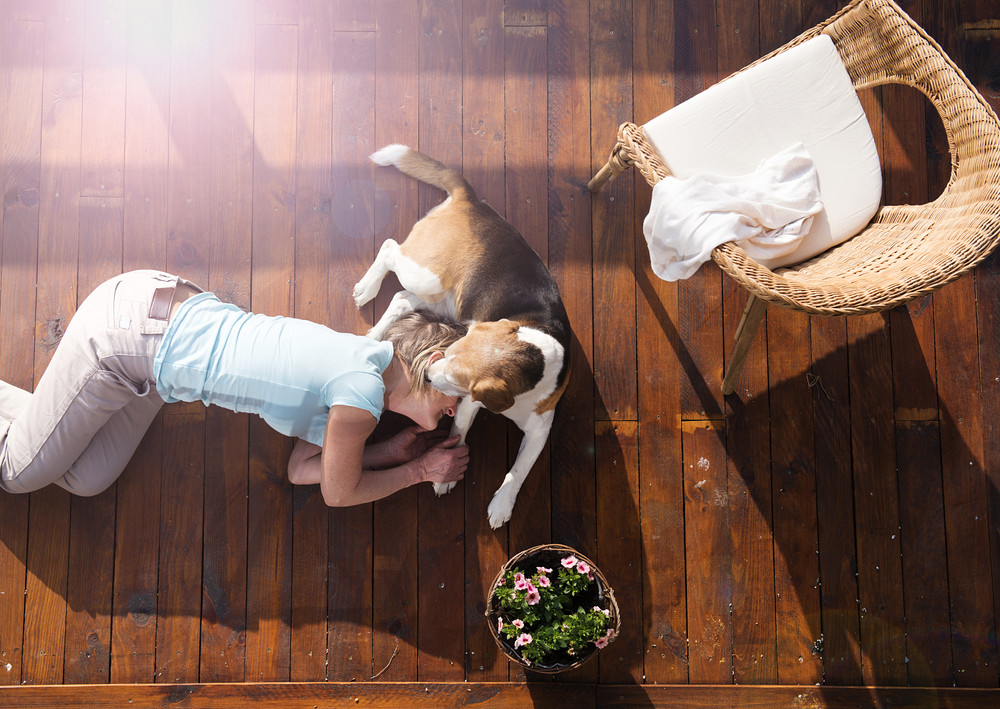 Senior woman with her dog on a terrace of her house.