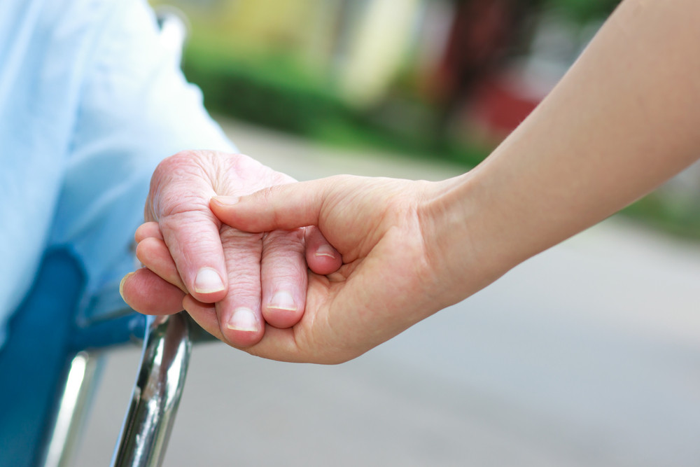 Senior women in wheelchair holding hands with caretaker