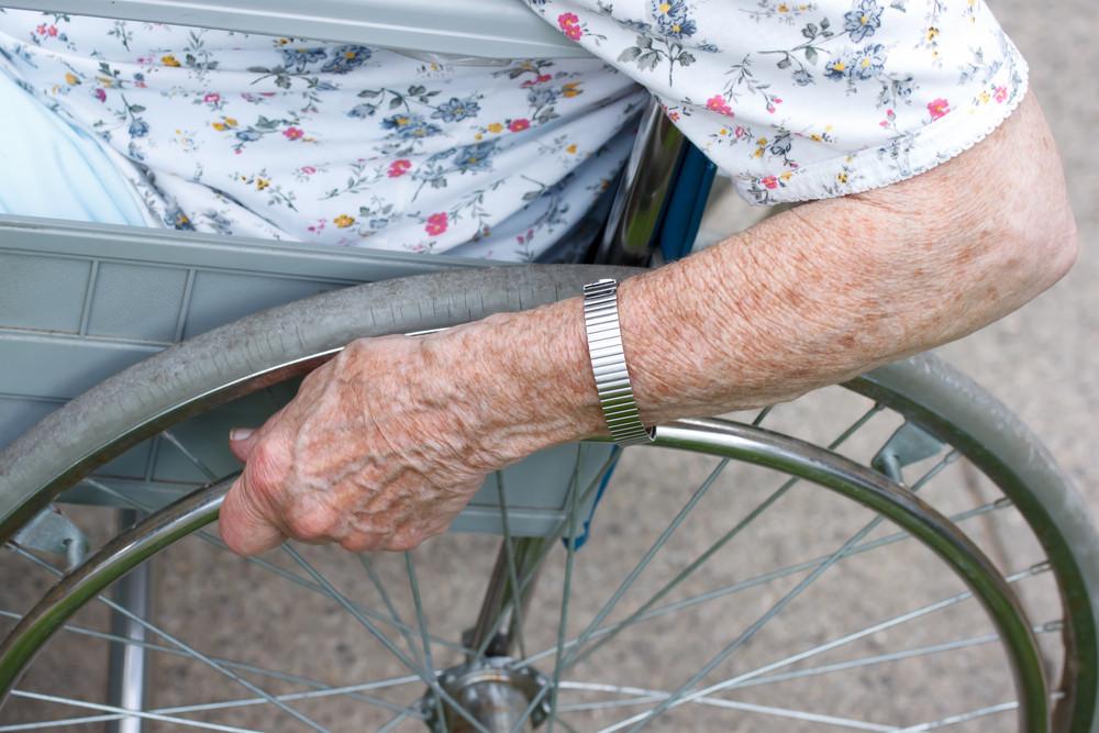 Senior's hand on wheel of wheelchair outside