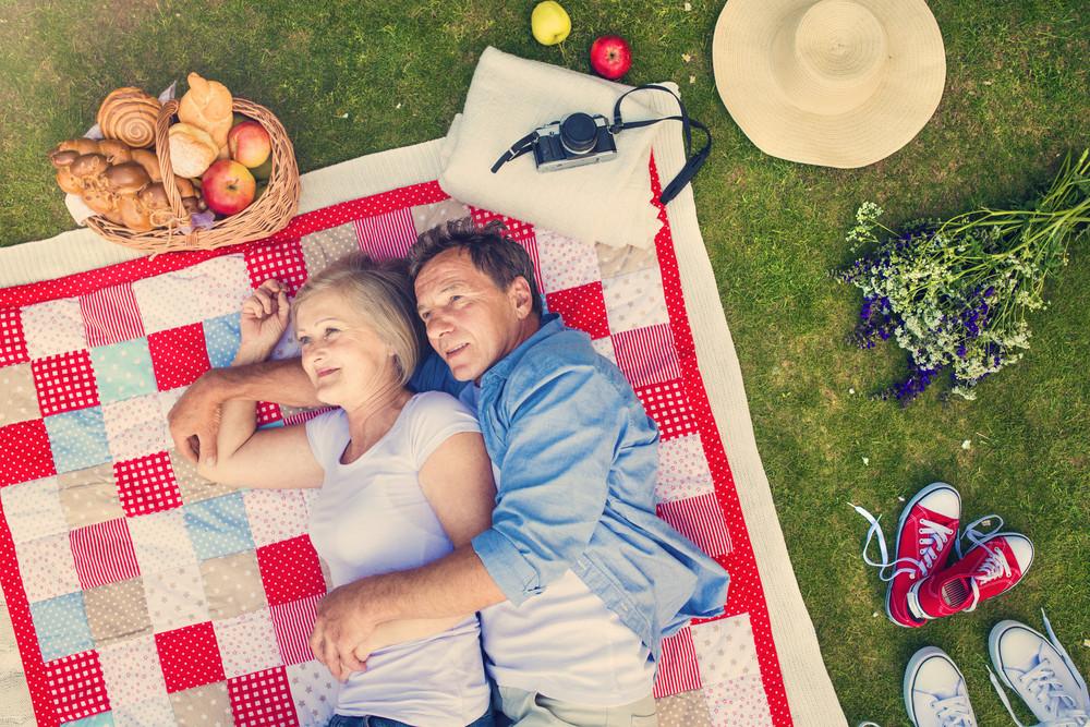 Seniors having a picnic lying on a colorful blanket