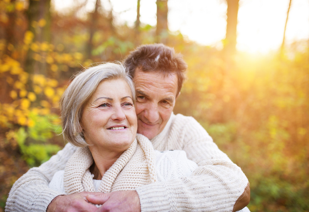 Seniors in love on a walk in autumn forest