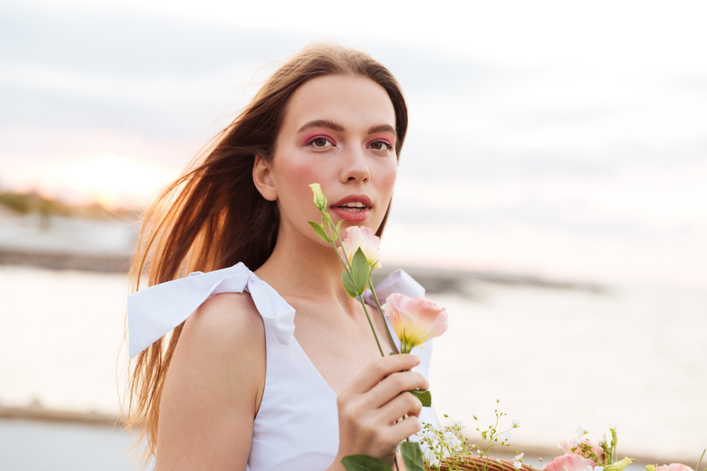 Sensual attractive young woman standing outdoors and holding flower