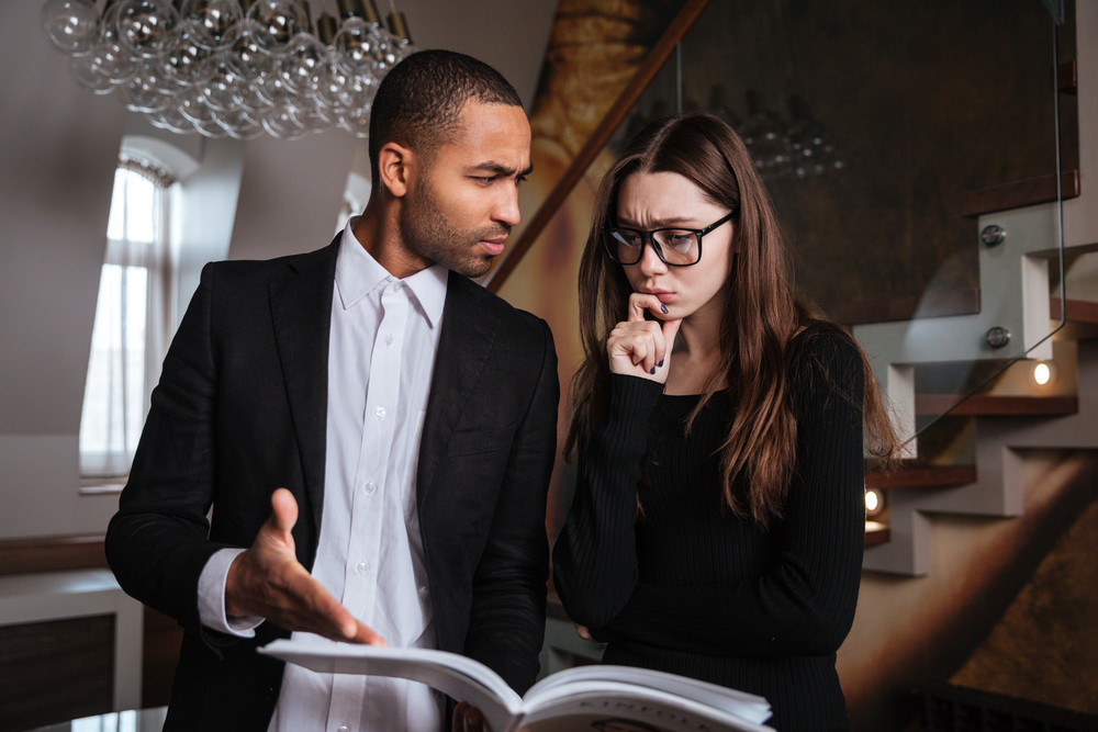 Serious African man in suit talking with woman in glasses and pointing at journal