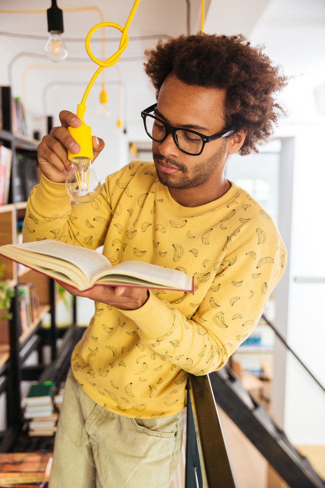 Serious african young man with light bulb standing and reading a book in library