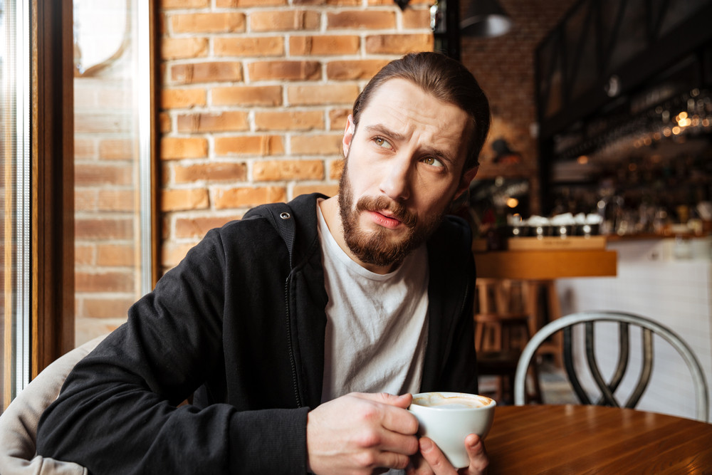 Serious Bearded man sitting in cafe with cup of coffee and looking away