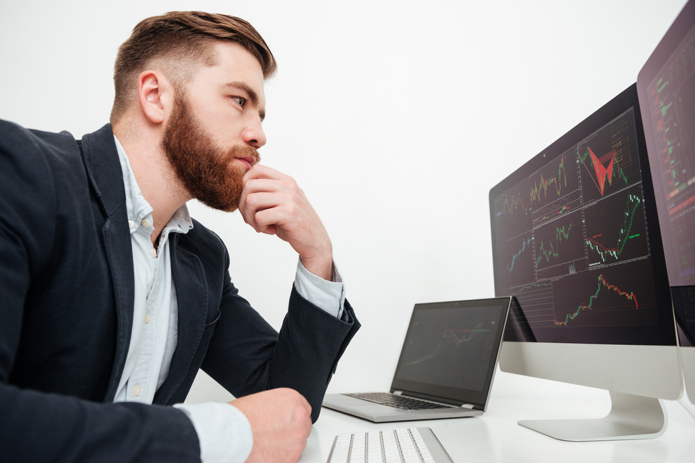 Serious bearded young businessman sitting and working with computer in office