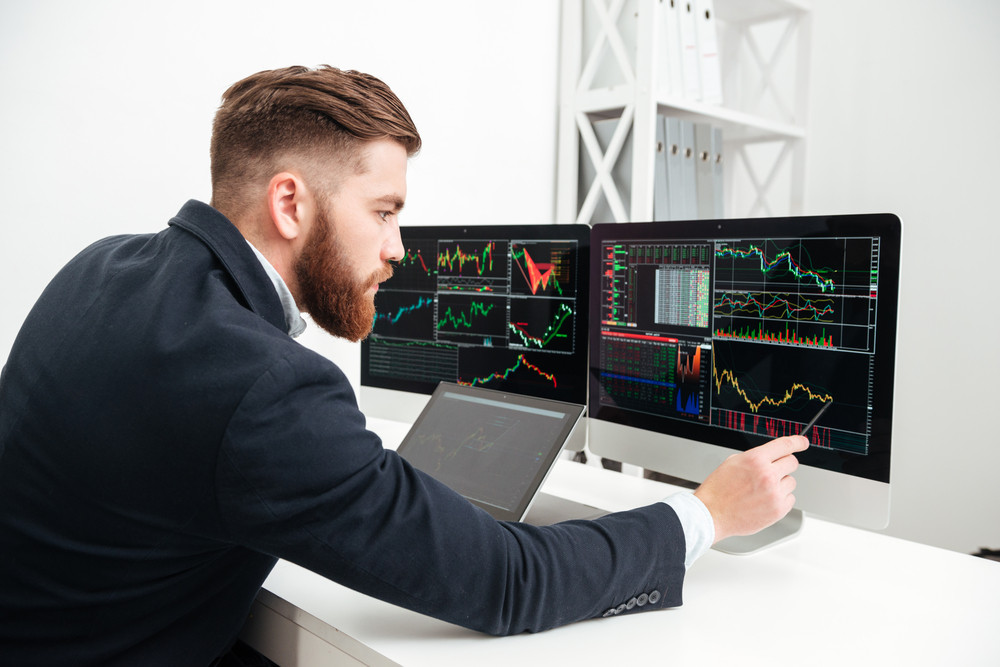 Serious bearded young businessman working with computer and making graphs in office