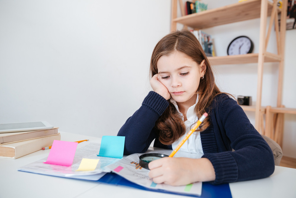 Serious little girl sitting and writing at the table in classroom