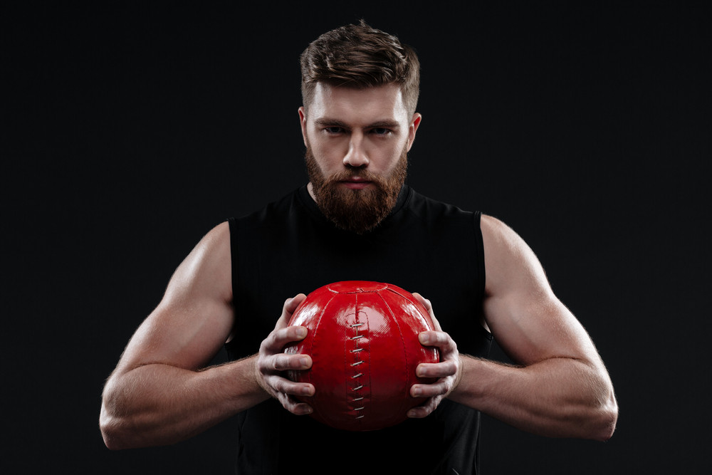 Serious trainer with ball. holding ball in hands. isolated dark background