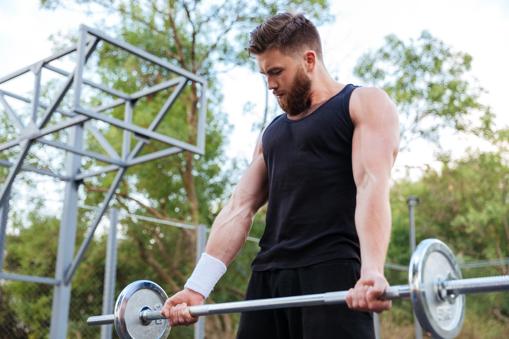 Serious young bearded fitness man lifting barbell outdoors