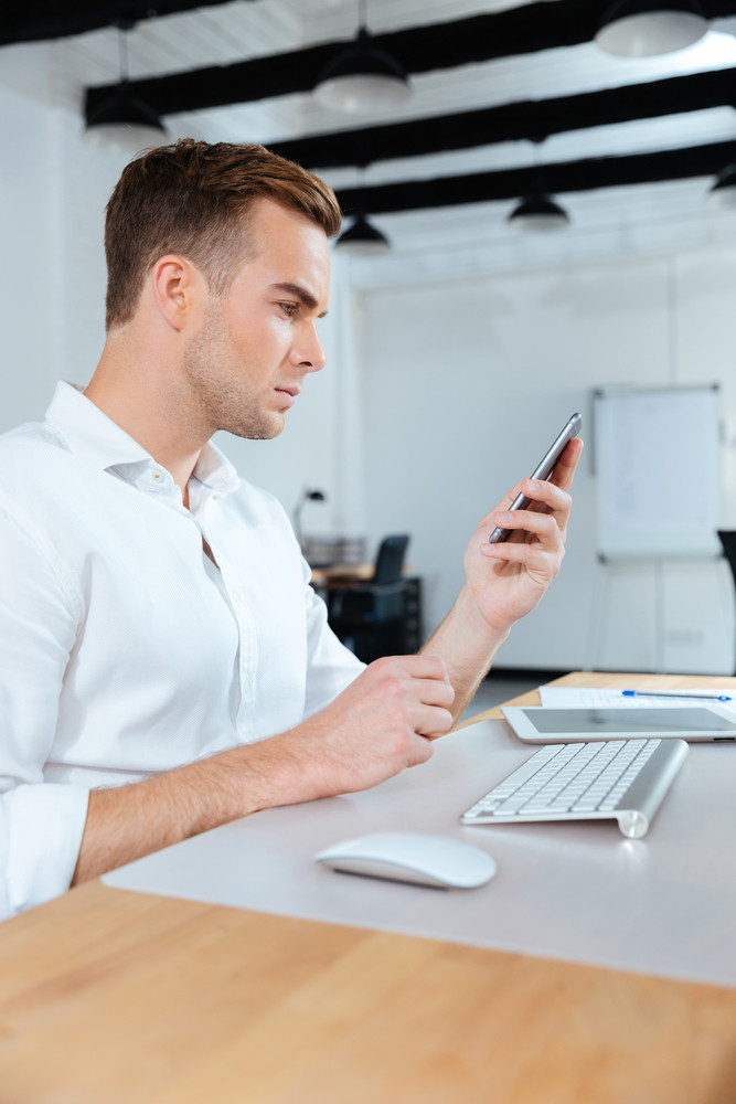 Serious young businessman sitting at workplace and using cell phone