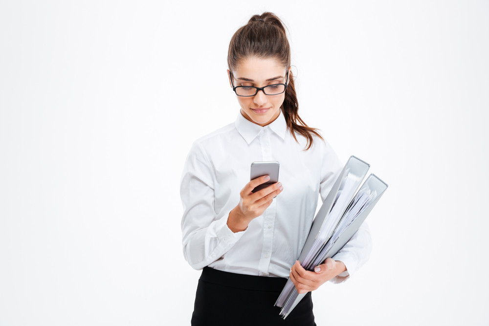 Serious young businesswoman in glasses holding folders and using smartphone over white background