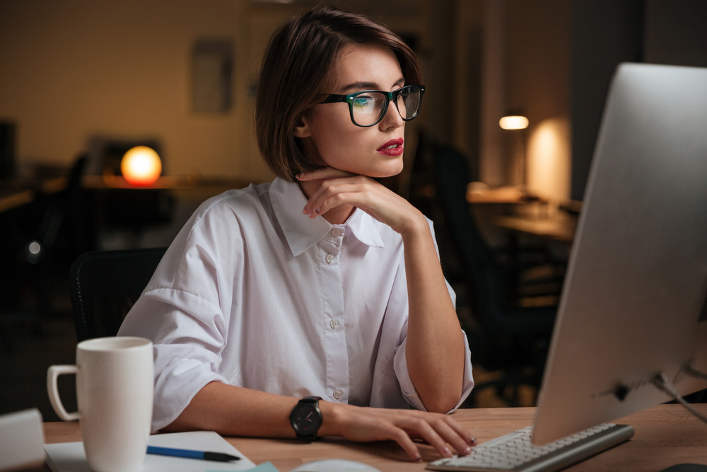 Serious young businesswoman in glasses sitting and working with computer in office