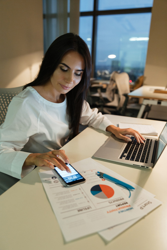 Serious young businesswoman using cell phone and laptop in office