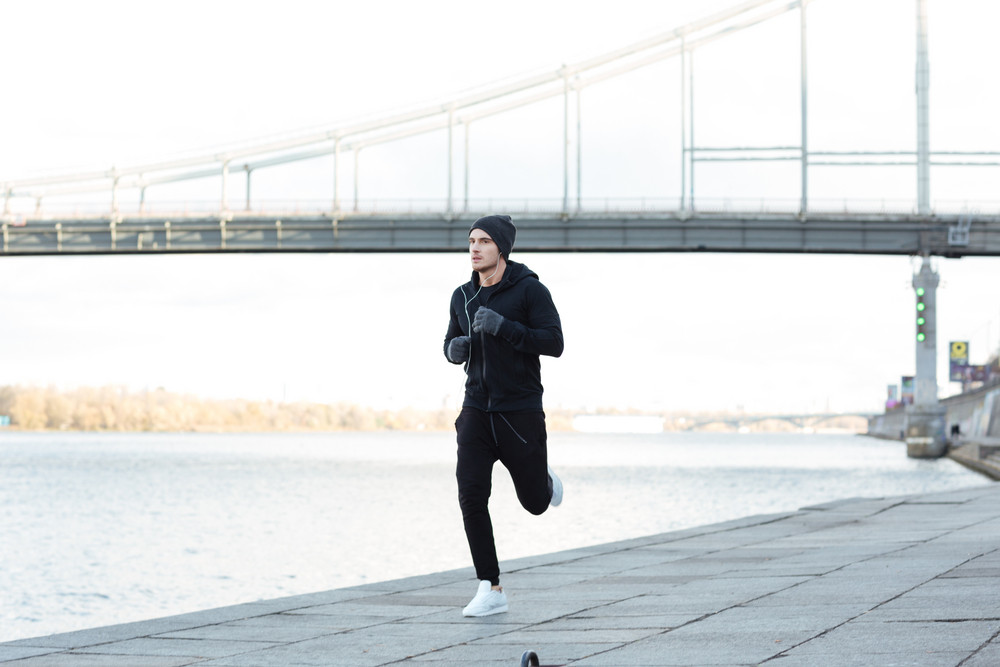 Serious young man athlete running outdoors in autumn