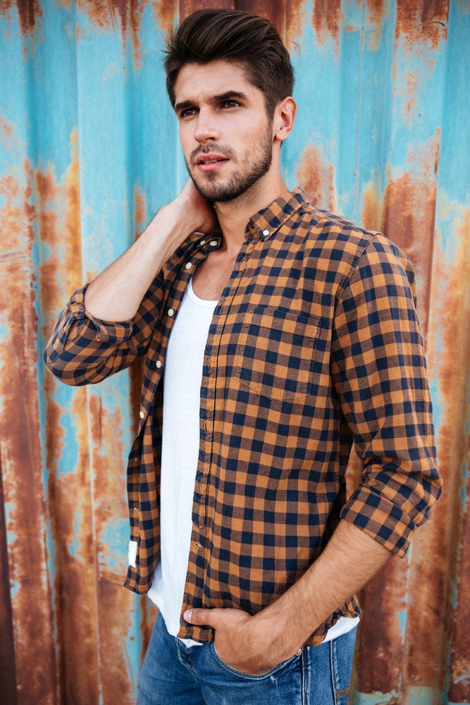 Serious young man in checkered shirt standing with hand in pocket over blue metal background with rust