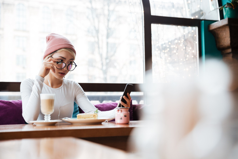 Serious young woman in hat and glasses eating and using cell phone in cafe