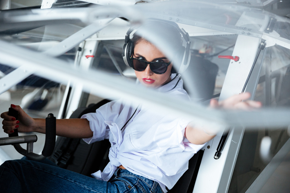 Serious young woman pilot in sunglasses and headset sitting in small aircraft