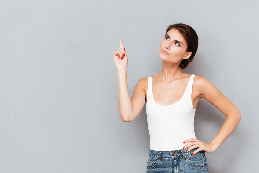Serious young woman pointing finger up over gray background