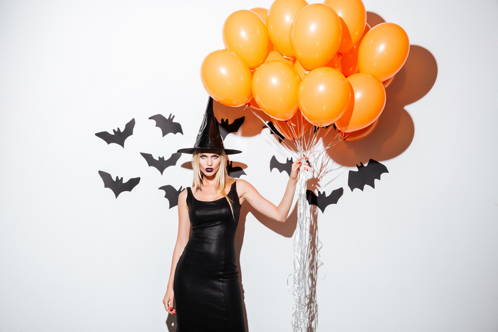 Sexy young woman in witch halloween costume standing and holding bunch of orange balloons over white background