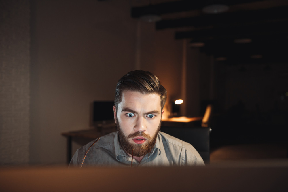 Shocked web designer dressed in shirt and holding eyeglasses working late at night and looking at computer.
