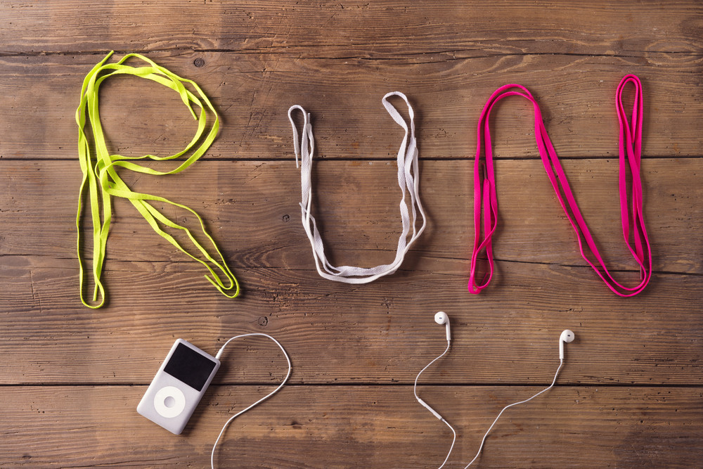 Shoelaces run sign and mp3 player on a wooden floor background