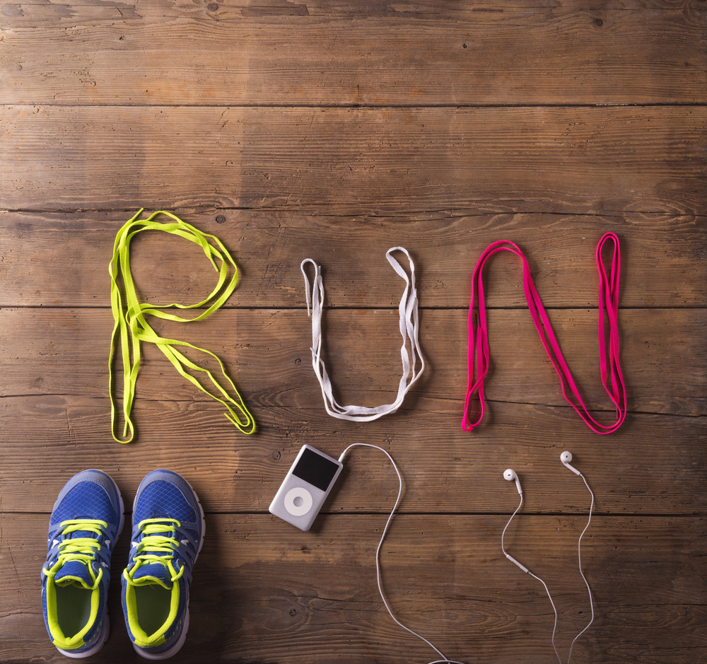 Shoelaces run sign, running shooes and mp3 player on a wooden floor background