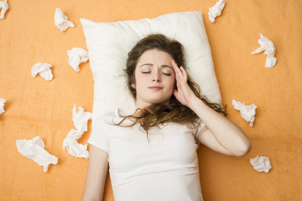 Sick woman lying in bed with cold and flu. She has a headache.
