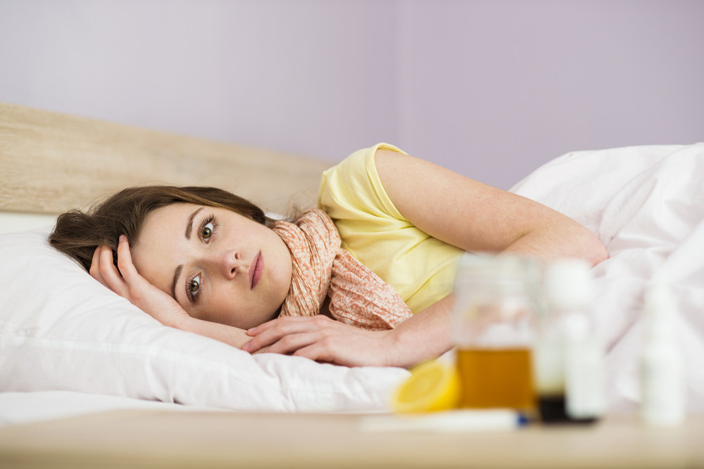 Sick woman lying in bed with high fever. She has cold and flu. In front of her is tea with lemon and honey.