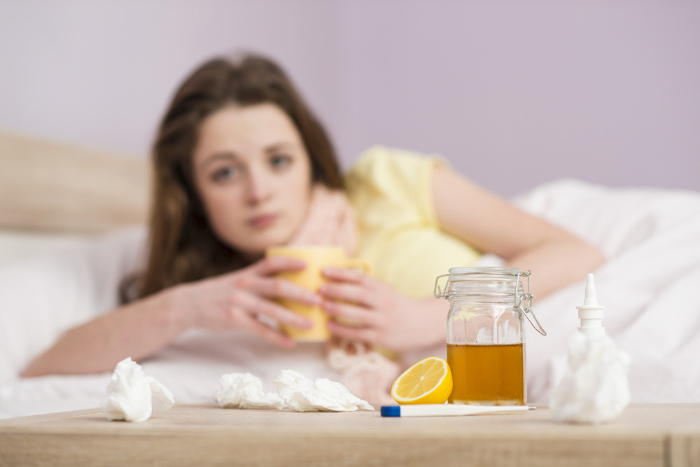 Sick woman lying in bed with high fever. She has cold and flu. She is drinking tea with honey and lemon.