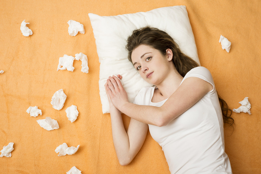 Sick woman lying in bed with sore throat. She has cold and flu.
